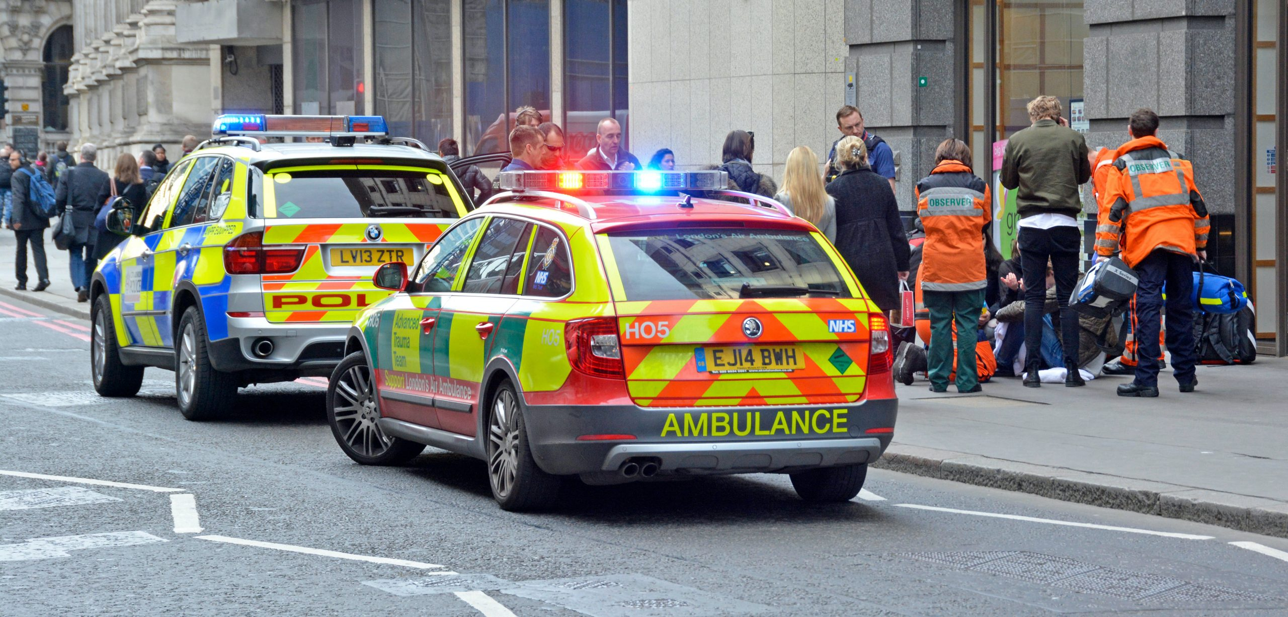 EJ6AMG Medics and police with onlookers around a pedestrian on pavement requiring medical assistance with parked emergency vehicles